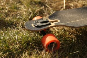 The nose of an electric skateboard with orange wheels on the grass