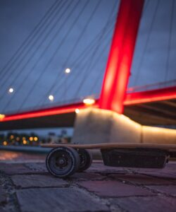 An electric skateboard at night in front of a lit up bridge