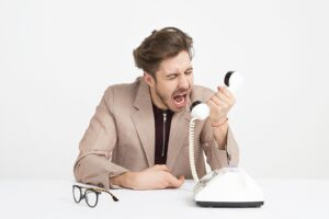 man yelling into a white landline phone