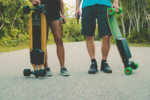 two people holding up electric skateboards